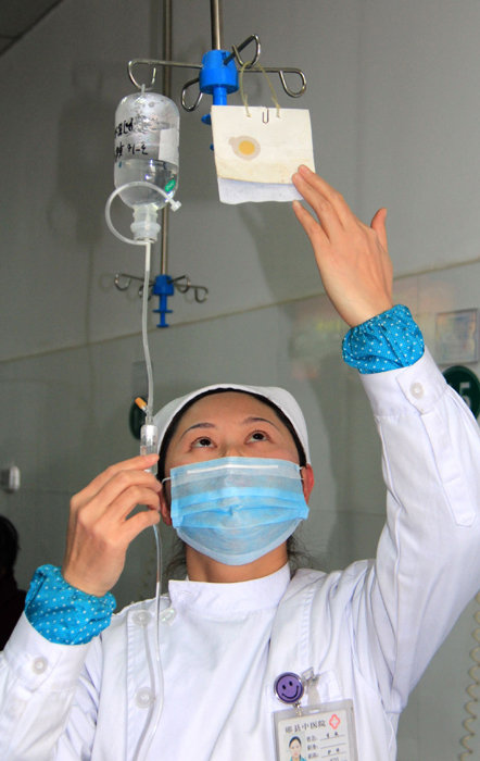 省十堰市郧县中医院的一名护士在为患者输液.新华社发(曹忠宏 摄
