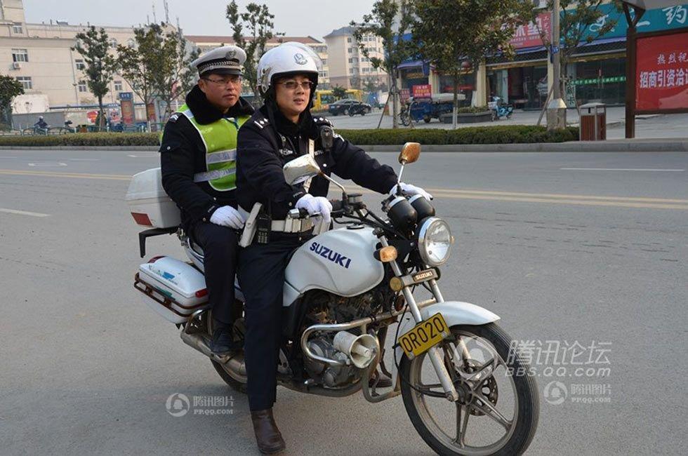 午学生放学时的交通高峰期,殷飞华跟另一交警骑着摩托巡查路段,