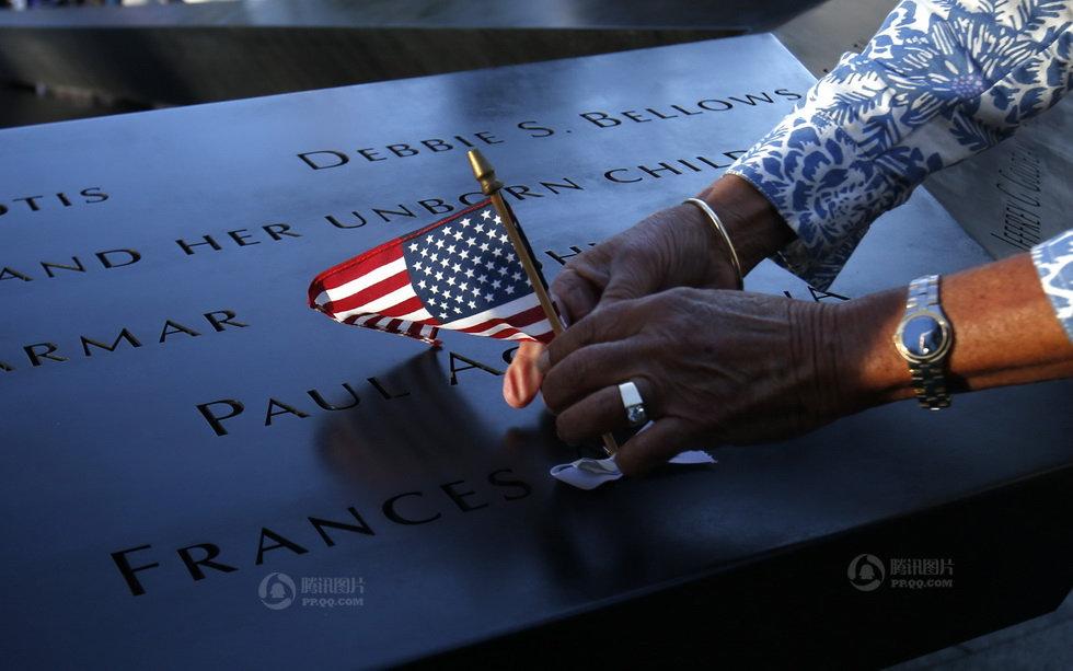 一名市民将一面美国国旗放置于遇难者的姓名上(2012年9月11日摄