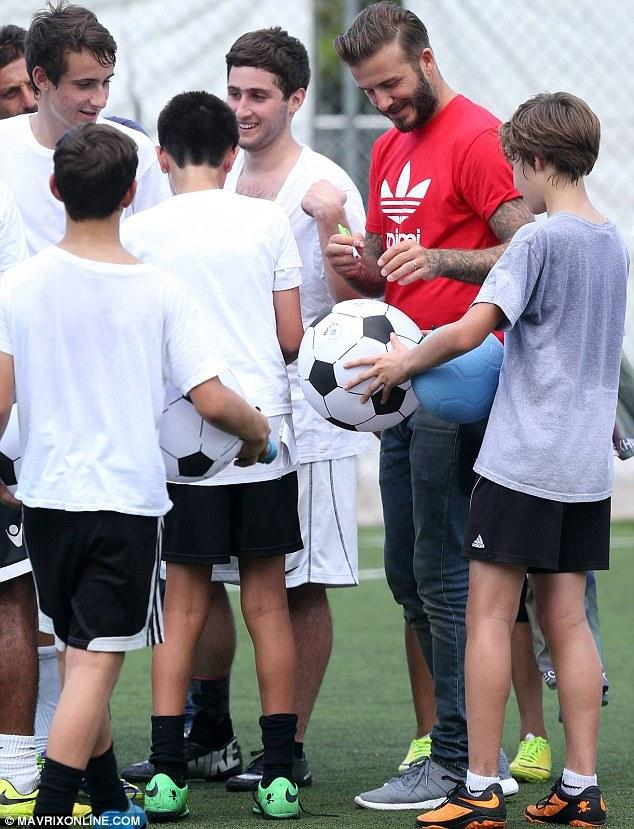 小贝现身少年足球训练营 签名合照显亲和