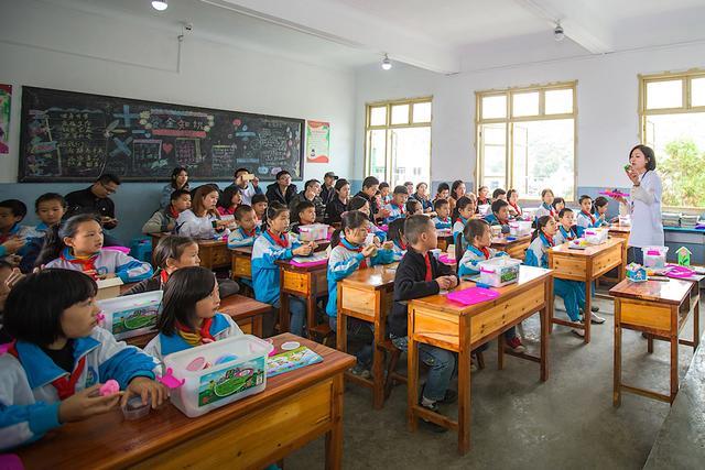 光照小学的孩子们在明亮的教室里兴趣盎然地听新来的美术老师讲课