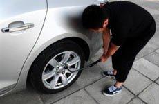 2、将需要更换车轮的螺栓略微松开,螺栓固定较紧时可以用脚踩轮胎扳