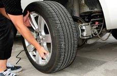 4、摇动千斤顶将车身支起,然后有扳手卸下需更换的轮胎的螺栓,卸下车轮。