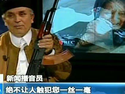 利比亚播音员持AK-47誓言保护卡扎菲