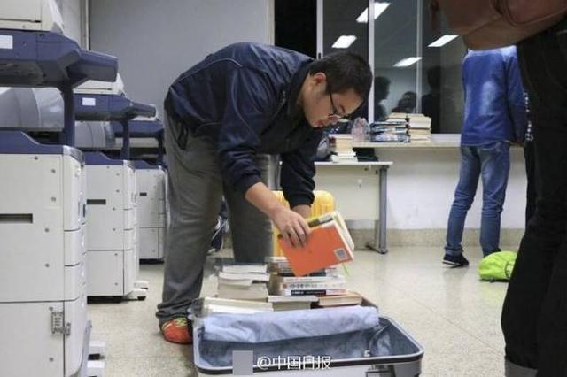 高校图书馆可借80本书 学生拖行李箱搬书
