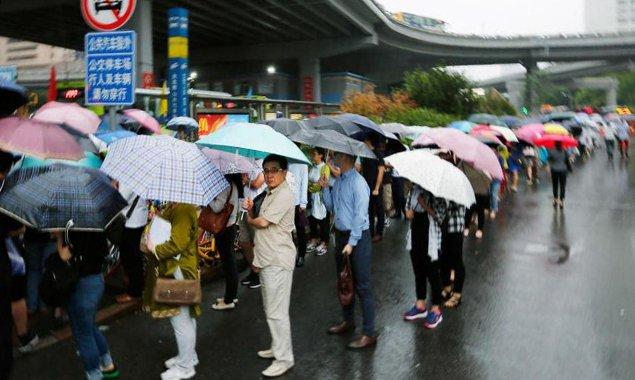乘客暴雨中排长龙等公交车回燕郊