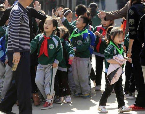 小学生戴绿领巾惹争议 评论称比抽教鞭更加恶毒