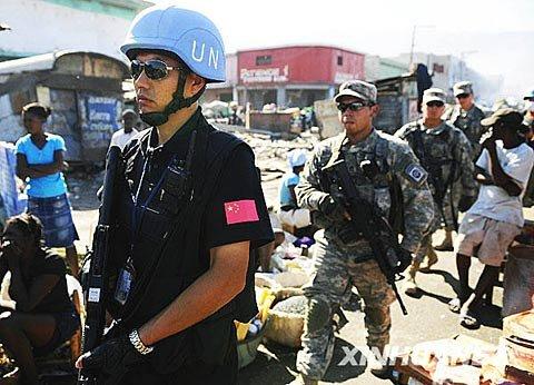一名中国赴海地维和警察防暴队队员(前)与美军士兵在街头巡逻。新华社记者 吴晓凌 摄