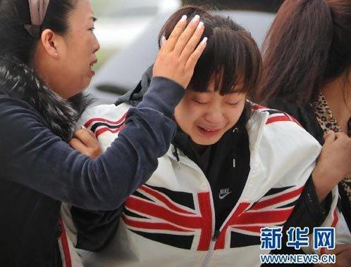 8月25日,一位在伊春空难中失去亲人的家属(中)在机场门前悲痛不已。