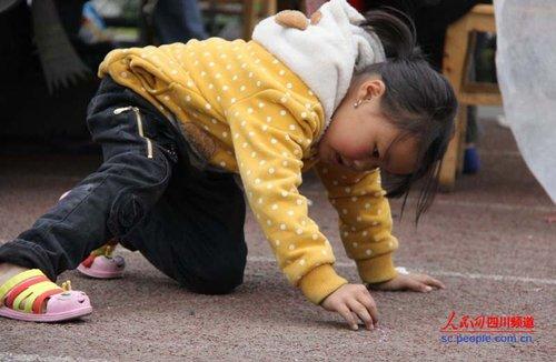 小女孩拿着粉笔在地上画画