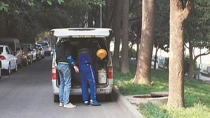 成都两男子挪开窨井盖舀地沟油 车上装满油桶(图)