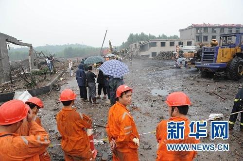 7月8日,几名救援人员在爆炸现场待命。新华社记者 赵鹏 摄