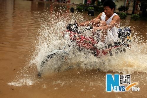 6月15日,南宁市一位男子骑着摩托涉水而行。新华社发(唐辉吉 摄)