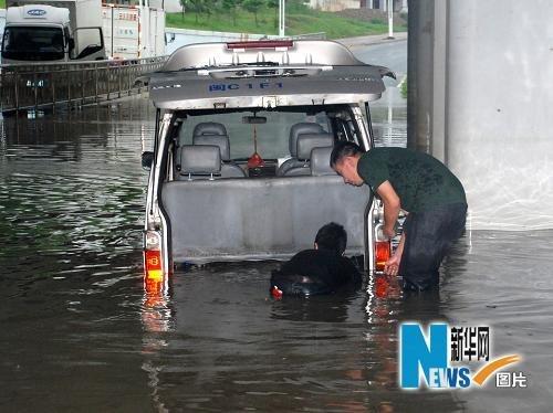 6月15日下午,在福建泉州市泉州大桥下,两位市民设法将困在积水中的汽车拖走。新华社发(颜财斌 摄)