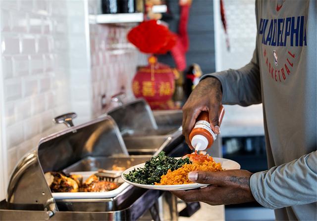 阿米尔-约翰逊在为食物装盘,他要带着这份午餐去参加球队会议