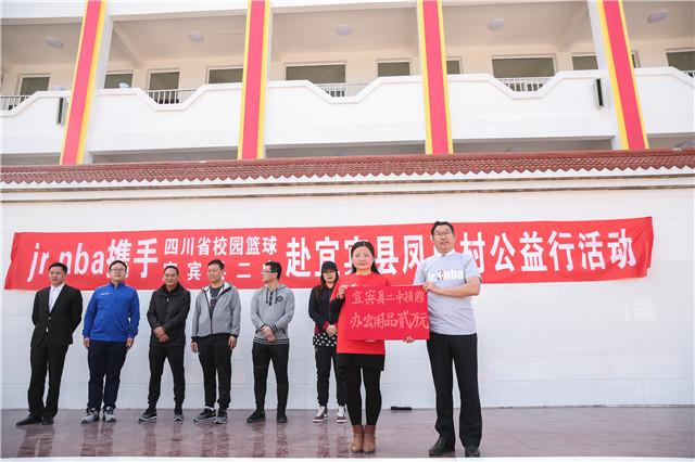 宜宾县二中徐同烈校长(右)向吕新姣校长捐赠价值两万元的办公用品