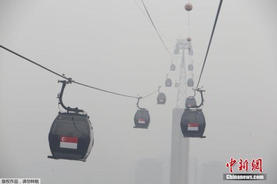 当地时间9月29日,新加坡依旧笼罩在雾霾之中,从高空俯瞰下去,城市陷入一片朦胧之中。通往旅游区的观光缆车在雾霾中正常运转,但往日美景已经看不到了。