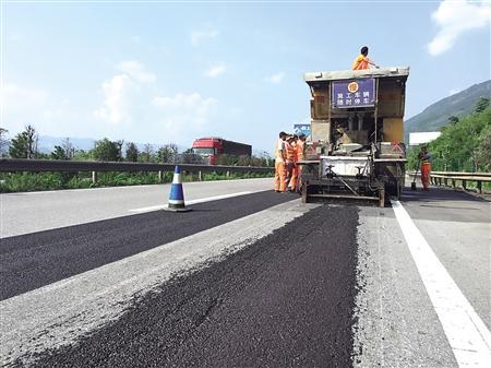 G65包茂高速渝湘路施工现场,工人们在路边加铺新型防滑沥青.