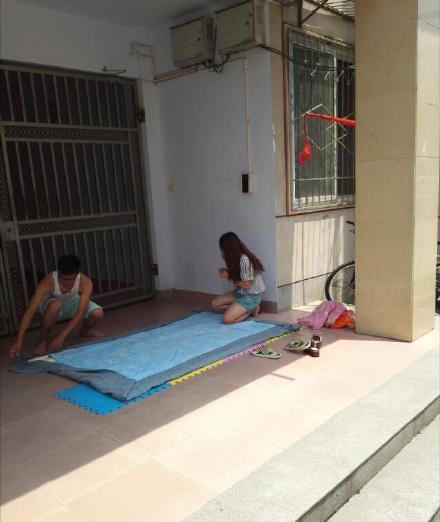 女大学生在宿舍楼下给男友缝被子(图)