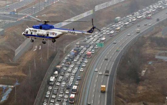 2015年2月18日,韩国京畿道城南市的京釜高速公路首尔收费站附近路段,大批返乡过春节的车辆拥堵在高速公路上。东方IC 图