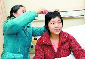 24日,临江门,附二院,妈妈石昌琼在给女儿廖良梅梳头发. 王海 摄-