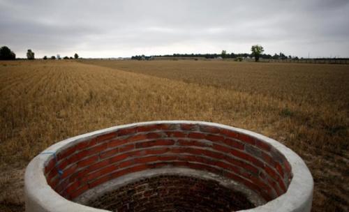 在西班牙阿雷瓦洛的一处农田,高温已造成农作物一片枯黄,连水井也干枯了。(路透社)