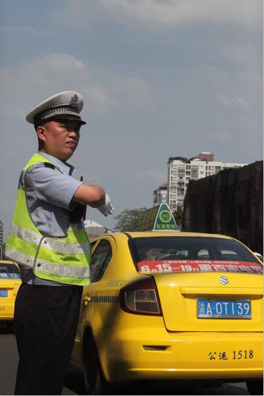 九龙坡交巡警战高温:车流中忍受热浪 抽空喝防暑药