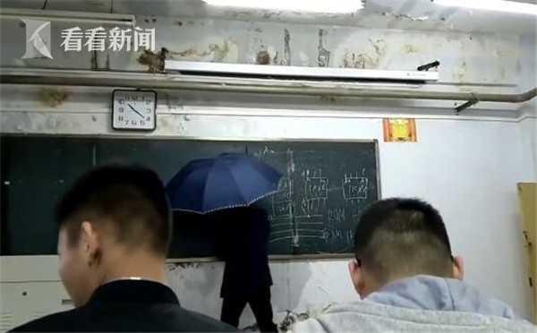 心疼!高校教室屋顶漏雨 老师雨中打伞上课