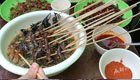 一大学考试现场学生围吃昆虫