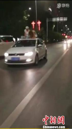 西安一对男女酒后坐车顶兜风 交警已进行处罚