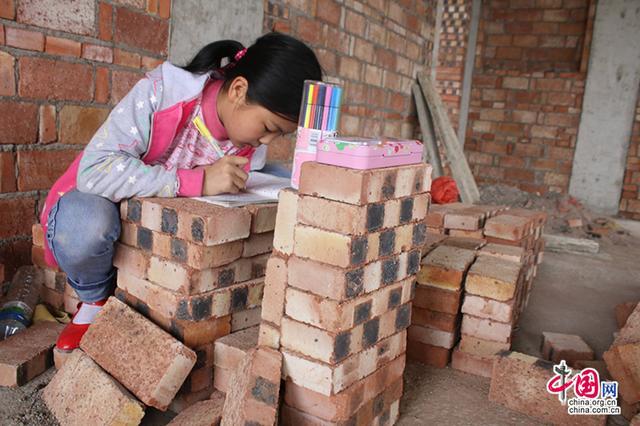 周末随父母上工地 女孩垒砖作课桌写字看书