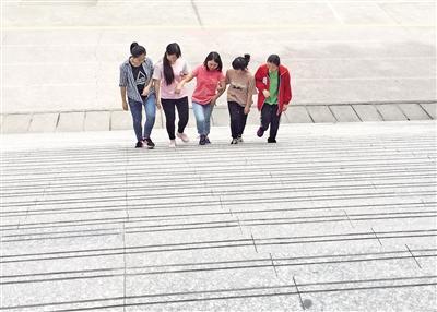 从小腿脚不方便 4位同学轮流背她上下学