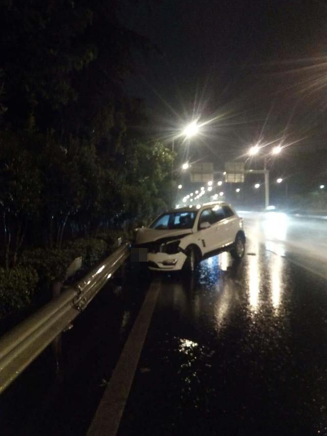 司机雨夜着急去打牌 边开车边打手机撞上路边护栏