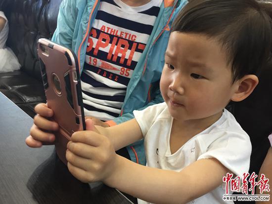 5月14日,天津一家餐厅,一名3岁儿童在等餐期间,用家长的手机聚精会神玩儿游戏。中国青年报·中青在线记者  张国/摄