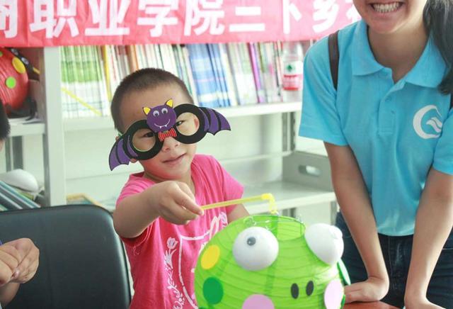 小朋友在志愿者的指导下,diy眼镜,灯笼等手工品图片