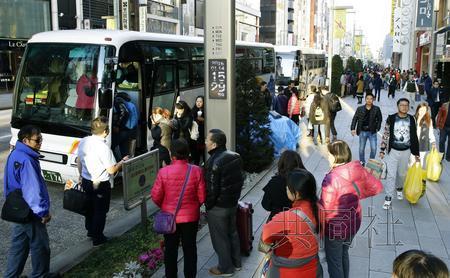 1月14日,东京银座街头,外国游客在免税店购物后登上旅游巴士。(共同社)