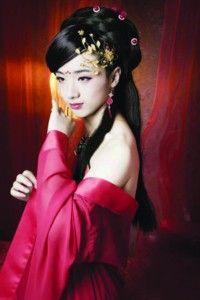 弯弯的柳叶眉,眉心几点樱花红;及腰长发,腰肢纤细;一袭红色丝绸裙搭配图片