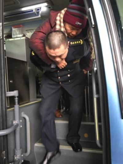 老人腿脚不方便 机场摆渡车司机背其上下车(图)