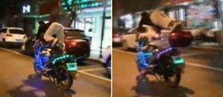 男子骑摩托车练杂技 单腿翘起做俯卧撑