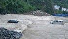 暴雨致两车被冲入河中