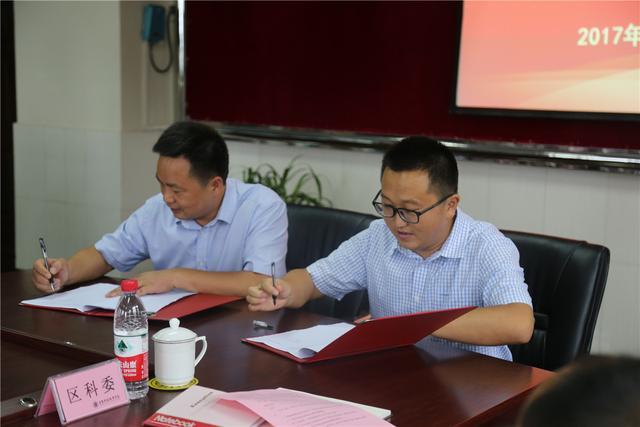 图6 区新城建管委党工委副书记、副主任毛希桥和重庆科创职业学院副校长代表双方签字