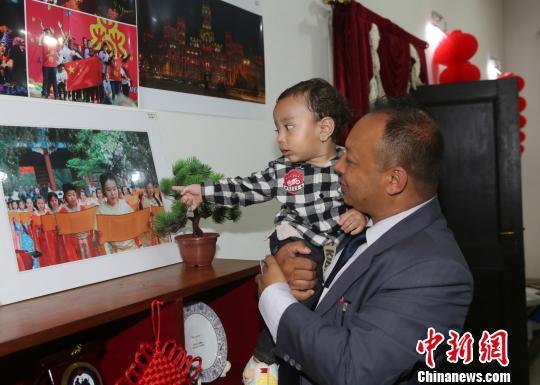 图为一对尼泊尔父子在欣赏有关中国的照片。 张晨翼 摄
