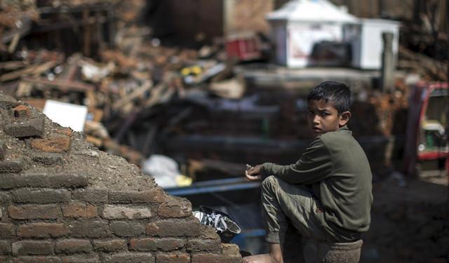 nkhu,一名男孩坐在地震废墟中.CFP供图-汶川七年,死亡威胁仍在