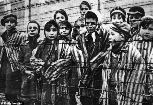 在奥斯维辛集中营里,一群孩子站在铁丝网的后面