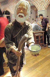 宜兰兰阳博物馆展览区,展示一座老乞丐人偶,穿着破衣拿个破碗,可怜
