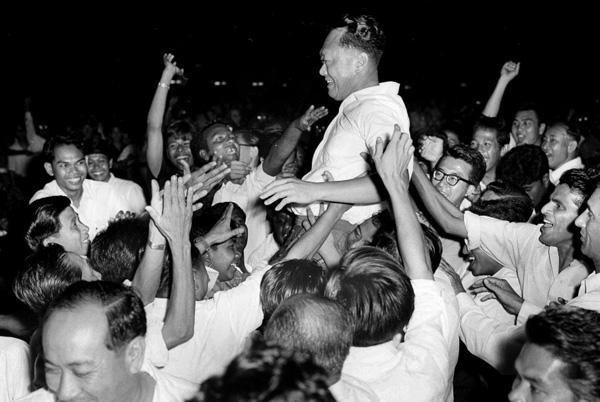 """李光耀在新加坡的""""国父""""地位是一步步积累起来的,图为赢得选战后,支持者将他抛起。"""