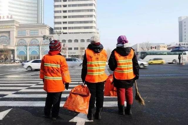 新闻图:被分派到哈尔滨南岗区城管局保洁一大队的两名研究生(中、右)在巡街保洁时过马路
