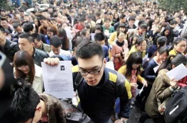 新闻图:江苏省公务员考试前,一名考生举着准考证进入考场。