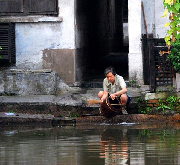江南阿婆在河边刷旧式马桶
