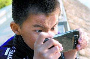 一位小学生在专心地玩手机.记者何波(资料